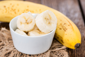 Banana Slices in a small bowl (on vintage background)